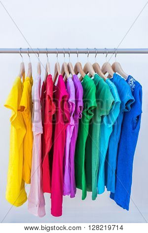 Fashion clothes on clothing rack - bright colorful stand of rainbow selection of t-shirts. Choice of trendy female wear on hangers in store closet or spring cleaning concept. Summer home wardrobe.