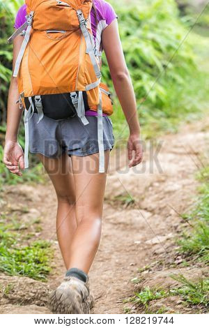 Hiker walking with orange backpack on hiking trail in forest nature on mountain path. Back view of shorts legs of trekking girl backpacking going up wearing boots on summer trip adventure activity.