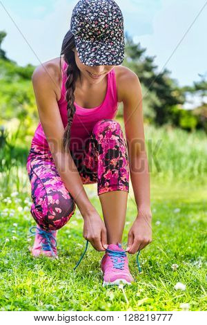 Cute sporty runner girl in fashion activewear wearing floral cap and pink leggings outfit getting ready for jogging tying laces running shoes on grass park. Fitness woman living active lifestyle.