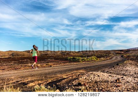 Trail runner female athlete running in dramatic volcano landscape on volcanic rocks path in summer nature mountains. Woman training hard in beautiful background. Travel destination.