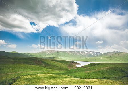 Green meadow, lake and blue sky with clouds. Exploring Armenia