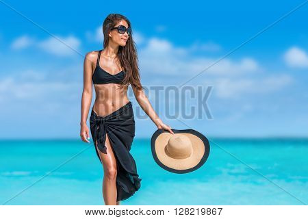 Elegant beach woman in bikini and fashion sarong standing on shore. Sexy lady in black beachwear, floppy hat, sunglasses enjoying sun on tropical destination during summer vacation in the Caribbean.