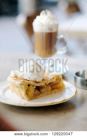 Latte with whipped cream and apple pie in outdoor restaurant