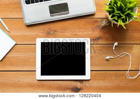 education, business, people and technology concept - close up of tablet pc computer, laptop and earphones on wooden table