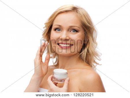 beauty, people, skincare and cosmetics concept - happy woman applying cream to her face