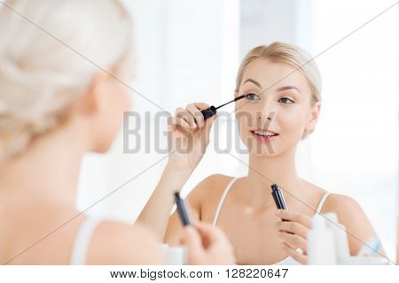 beauty, make up, cosmetics, morning and people concept - smiling young woman applying eye makeup with mascara and looking to mirror at home bathroom