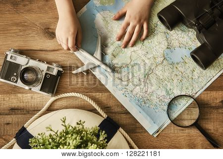 Go on an adventure! The map and the camera on a wooden table. Top view.