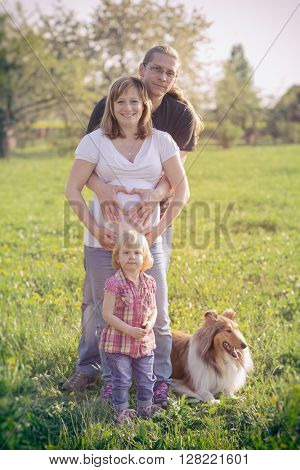 Pregnant Woman and Her Husband with her daughter holding her hands in a heart shape on her baby