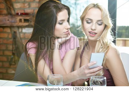 Two girls taking pictures on the phone at home