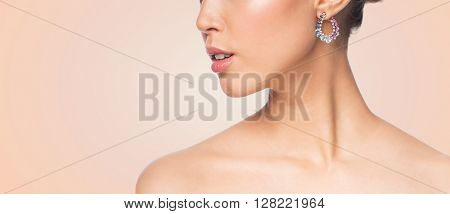 glamour, beauty, jewelry and luxury concept - close up of beautiful woman face with earring over beige background