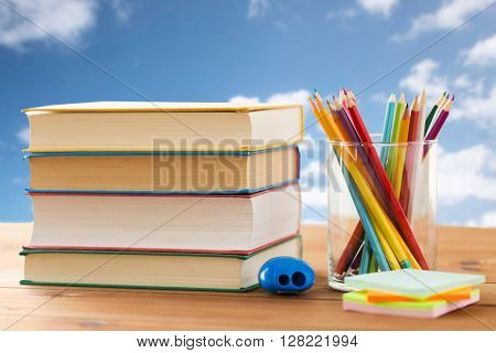 education, school, creativity and object concept - close up of crayons or color pencils with books, stickers and sharpener on wooden table over blue sky and clouds background