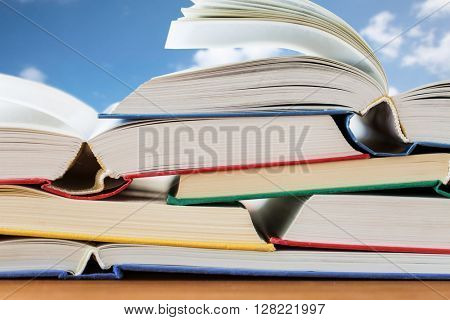 education, school, literature, reading and knowledge concept - close up of books on wooden table over blue sky and clouds background