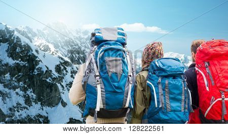 adventure, travel, tourism, hike and people concept - group of friends walking with backpacks from back over alps mountains background