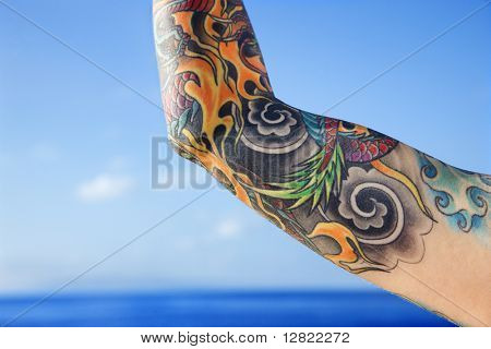 Close up of tattooed woman's arm with Pacific Ocean in background in Maui, Hawaii, USA.