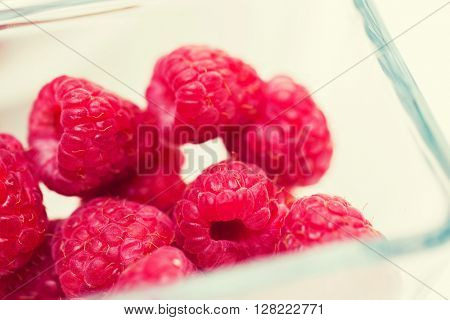 fruits, berries, diet, eco food and objects concept - close up of ripe red raspberries in glass