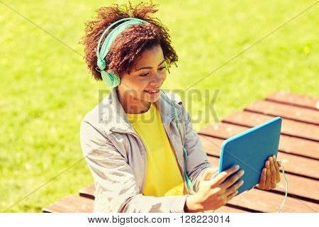 people, summer, technology and leisure concept - happy african american young woman in headphones with tablet pc computer listening to music or watching video outdoors