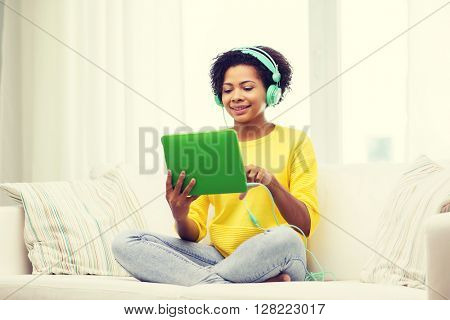 people, technology and leisure concept - happy african american young woman sitting on sofa with tablet pc computer and headphones listening to music at home