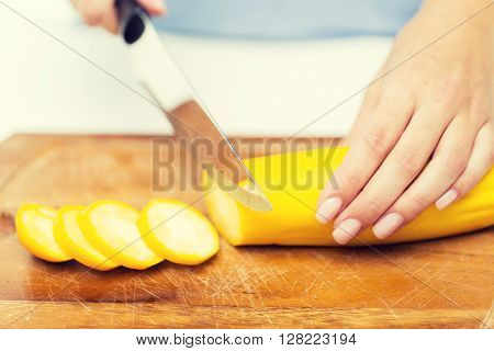 healthy eating, cooking, vegetarian food, vegetable and people concept - close up of woman hands chopping squash with knife on wooden cutting board