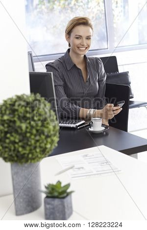 Happy young businesswoman working in green office, using mobilephone.