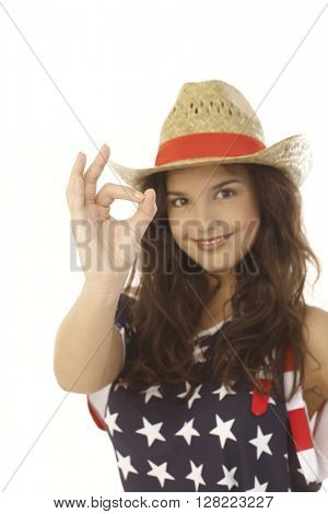 Happy young American woman showing okay sign, focus on hand.