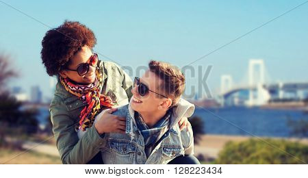 friendship, travel, tourism and people concept - happy international teenage couple in shades having fun over rainbow bridge at tokyo in japan background