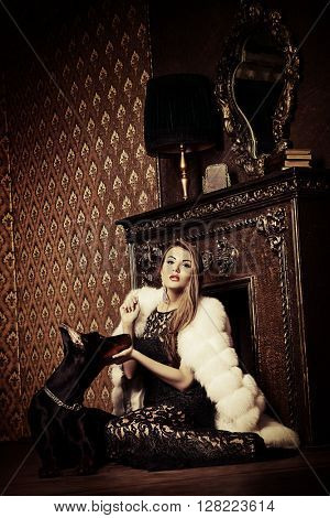 Beautiful woman in the precious jewelry and fur coat sitting by the fireplace with her dog. Classic interior. Beauty, fashion.