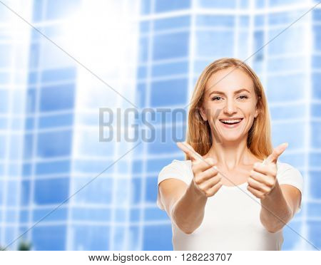 Happy businesswoman on the background of glass office building. Young smiling female outdoors showing sign ok
