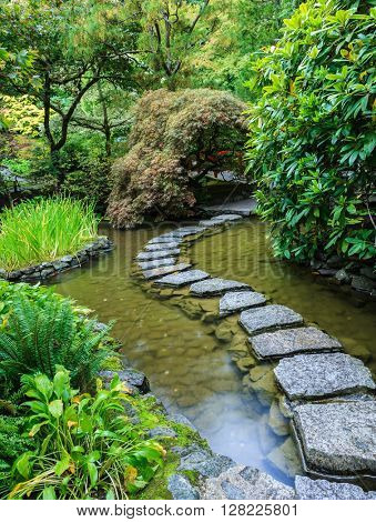 Decorative private garden on Vancouver Island in Canada - Butchart Gardens. The track of the stones in the water in the Japanese part of the garden