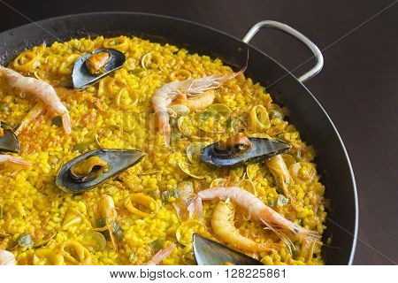 Spanish seafood Paella on a wooden table.