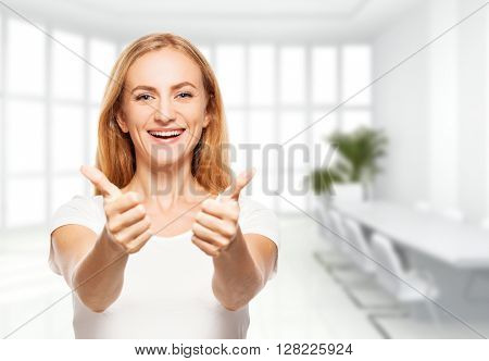 Happy businesswoman in the office. Young smiling female inside showing ok