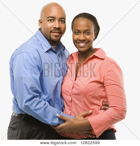 Portrait of African American couple with arms around eachother against white background.