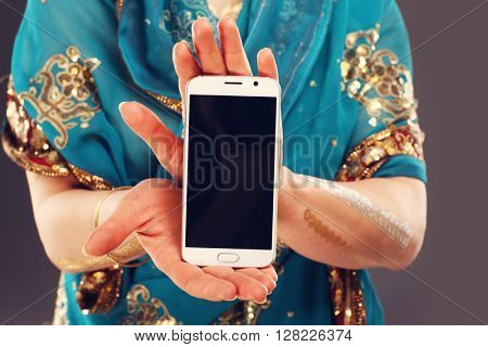 Midsection of oriental woman holding smartphone