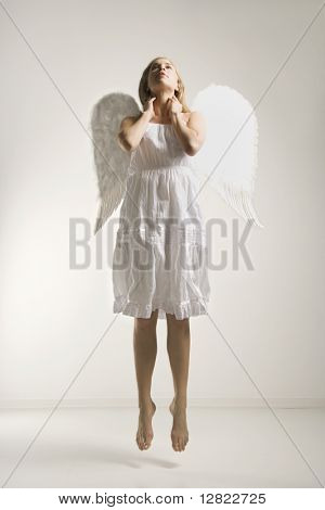 Caucasian mid-adult woman in white angel costume jumping in air.