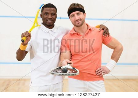 Group of best friends during squash match. Happy smiling man holding squash rackets and looking at camera on court.