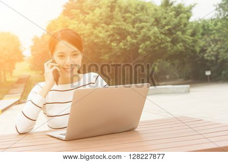 Woman working on laptop computer and use of mobile phone