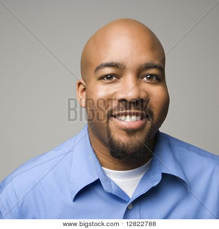 Retrato de hombre afroamericano sonriendo sobre fondo gris.
