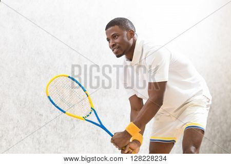 Male tennis player holding racquet on court. Handsome man playing squash game indoors. Sports concept.