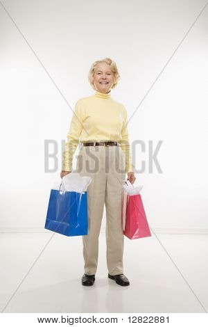Caucasian senior woman holding gift bags smiling at viewer.