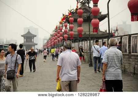 August 19 2015. Xian China. Chinese tourists walking on the city wall of Xian located in Shaanxi province China under a pollution filled sky.