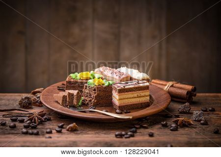 Different pastries on wooden plate, studio shot