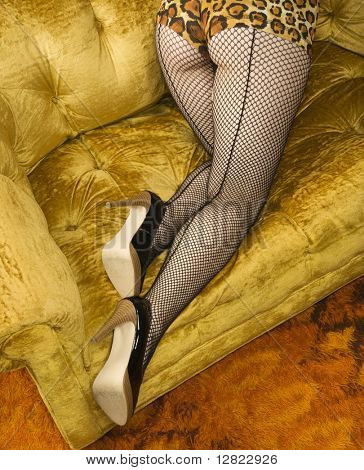 Pretty Caucasian woman in lingerie and fishnet stockings on sofa.