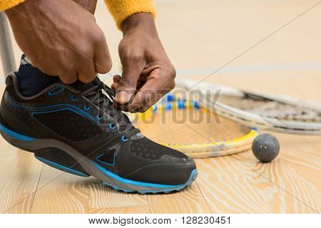 Black squash player man adjusting his training shoes preparing for squash game indoors. Squash racket and one ball are near by him.