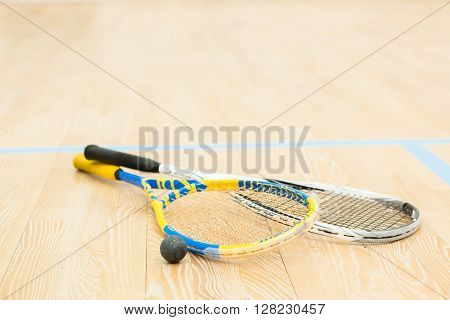 Closeup of squash rackets and one ball on wooden floor. Special equipment for squash game is ready.
