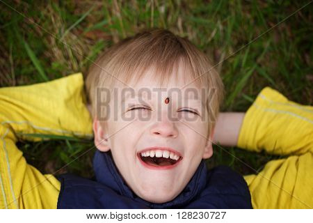 Beautiful little boy lies on meadow and smiling with ladybug on a forehead. Top view.