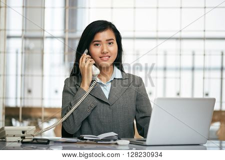friendly smile of front desk businesswoman telephoning the client