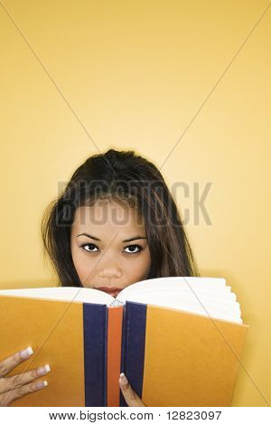 Filipino young adult woman peering over book at viewer.