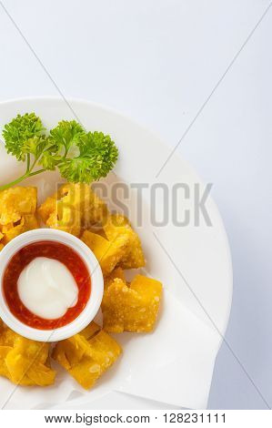 Chinese style deep-fried wonton with sweet and sour sauce in ceramic dish.