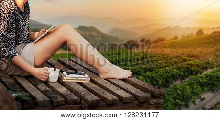 Morning scene of young hipster woman holding coffee cup by right hand and holding small tablet pc by left hand while sitting on wood litter on weekend with mountain view in blurry background