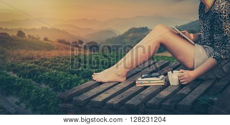 Morning scene of young hipster woman holding coffee cup by right hand and holding small tablet pc by left hand while sitting on wood litter on weekend with mountain view in blurry background processed with vintage filter effect