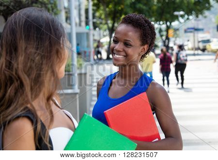 African american female student talking to caucasian girlfriend outdoor in the city